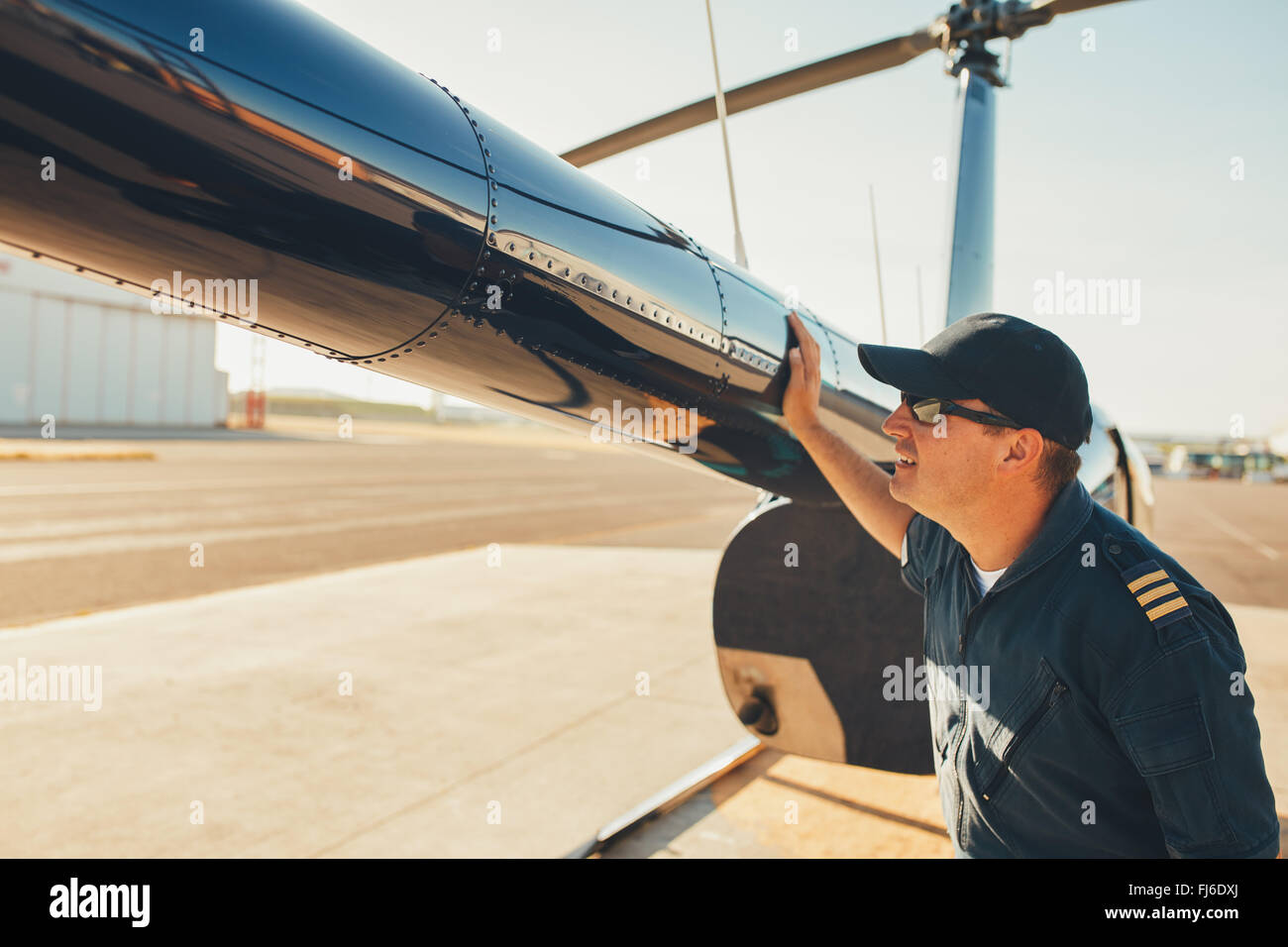 Male pilot checks the tail of helicopter before the flight. Mechanic checking helicopter before take off. - Stock Image