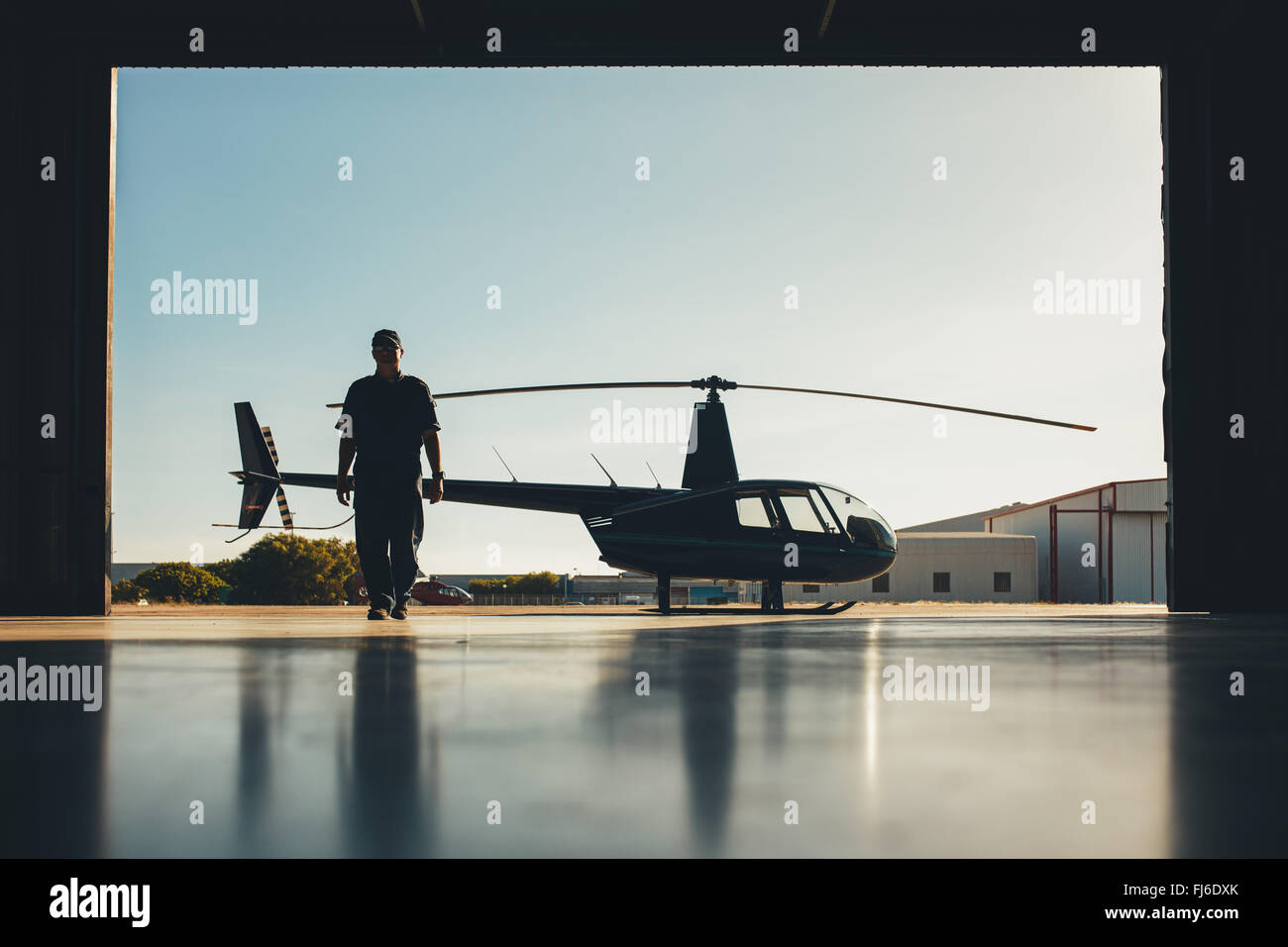 Silhouette of helicopter with a pilot in the airplane hangar. Pilot walking away from helicopter parked outside - Stock Image