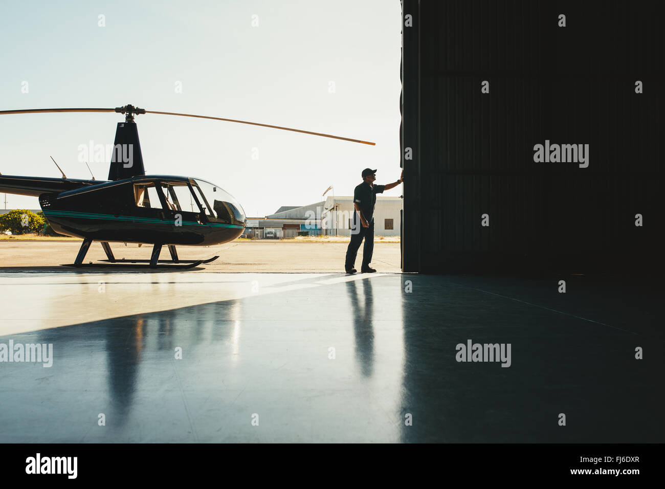Mechanic opening the door of a airplane hangar with a helicopter - Stock Image