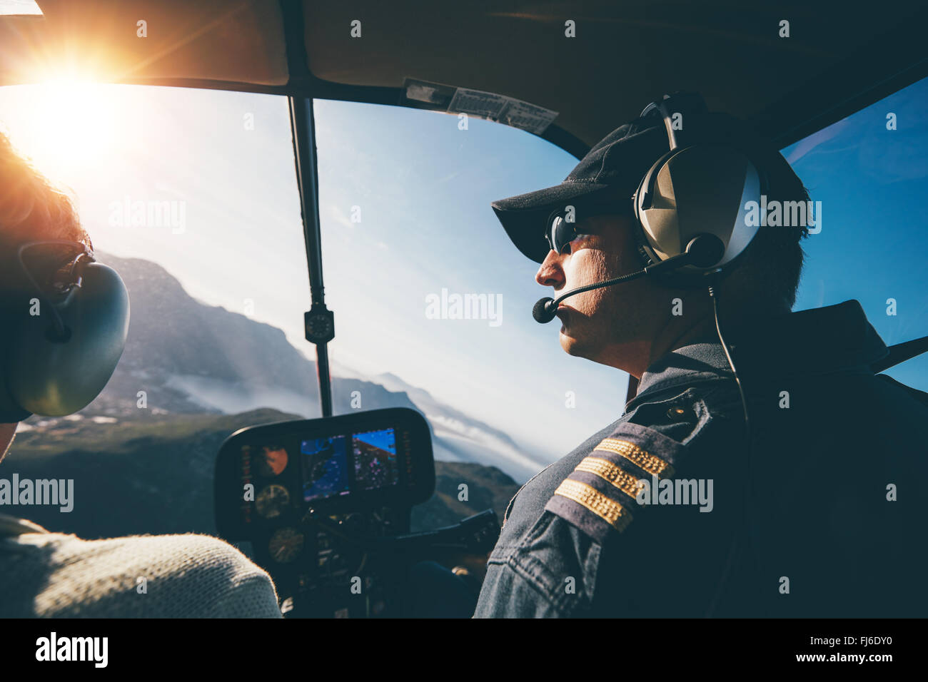 Man and woman pilots flying a helicopter on a sunny day. Inside shot of a helicopter. - Stock Image
