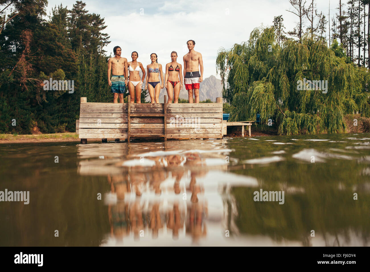 Portrait of group of young people standing on the edge of the pier on the lake. Young friends standing in a row - Stock Image