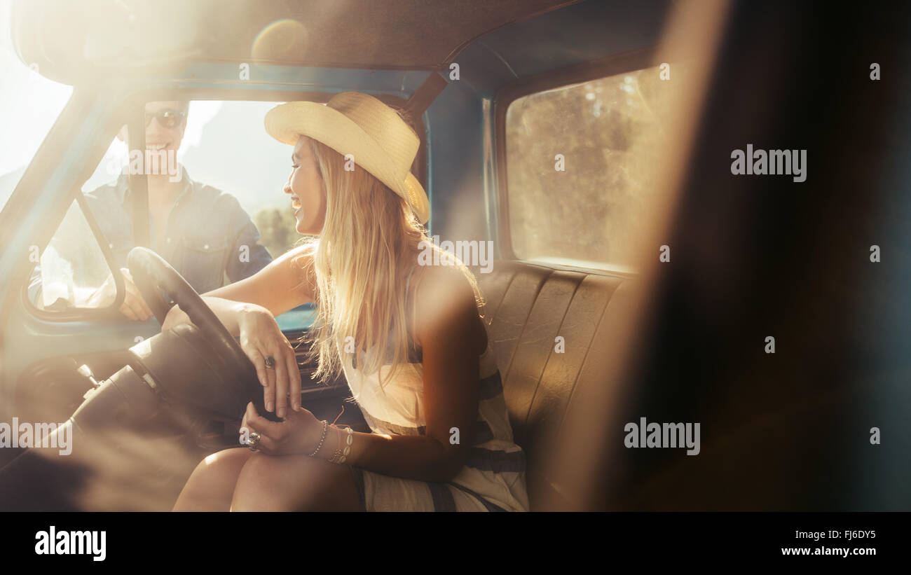 Portrait of young woman sitting in a car talking with friends standing by the car. - Stock Image