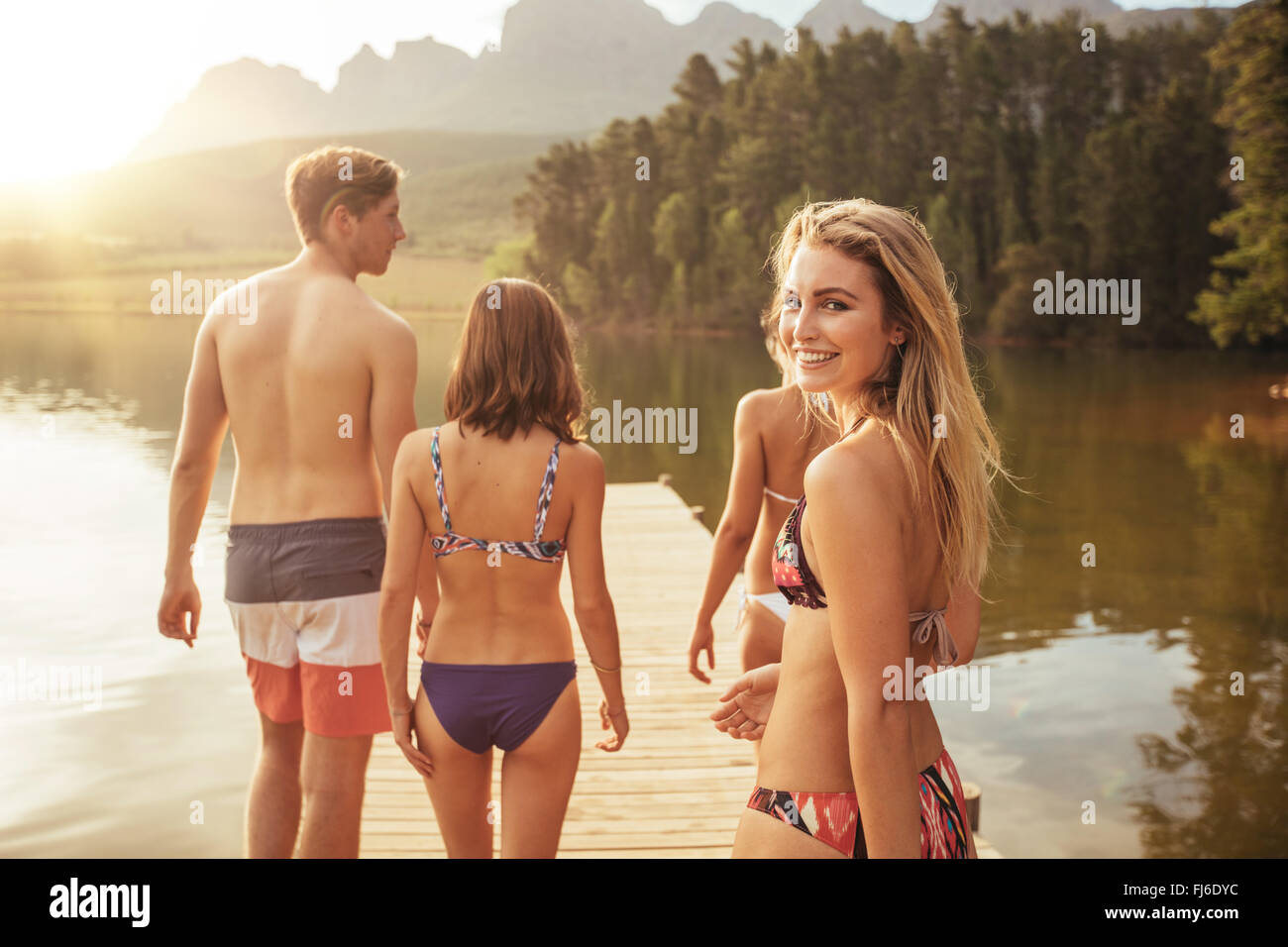 Portrait of beautiful young girl in bikini looking over her shoulder with her friends on pier. Group of young people - Stock Image