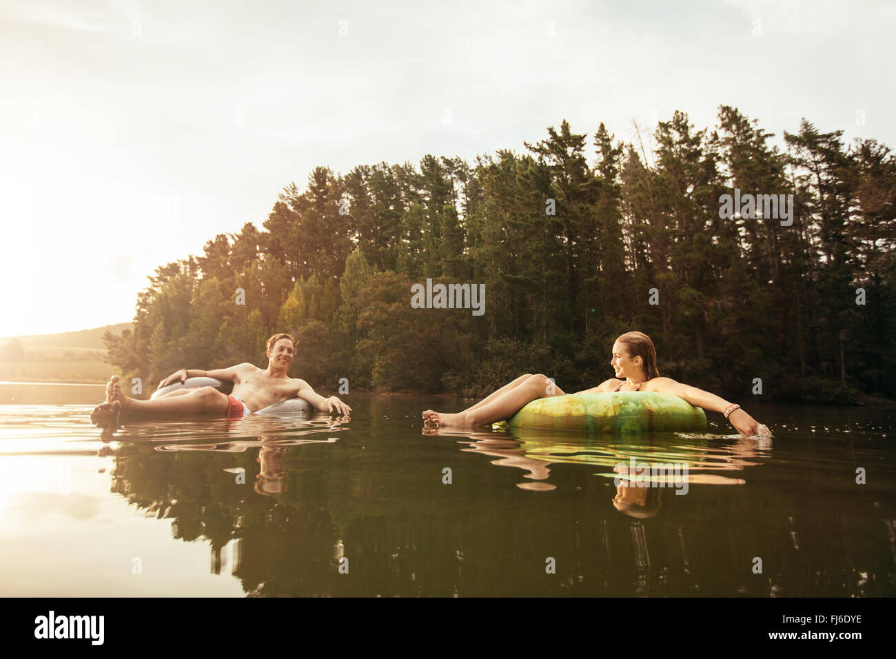 Portrait of young couple in lake on inflatable rings. Young couple relaxing in water on a summer day. Man and woman - Stock Image