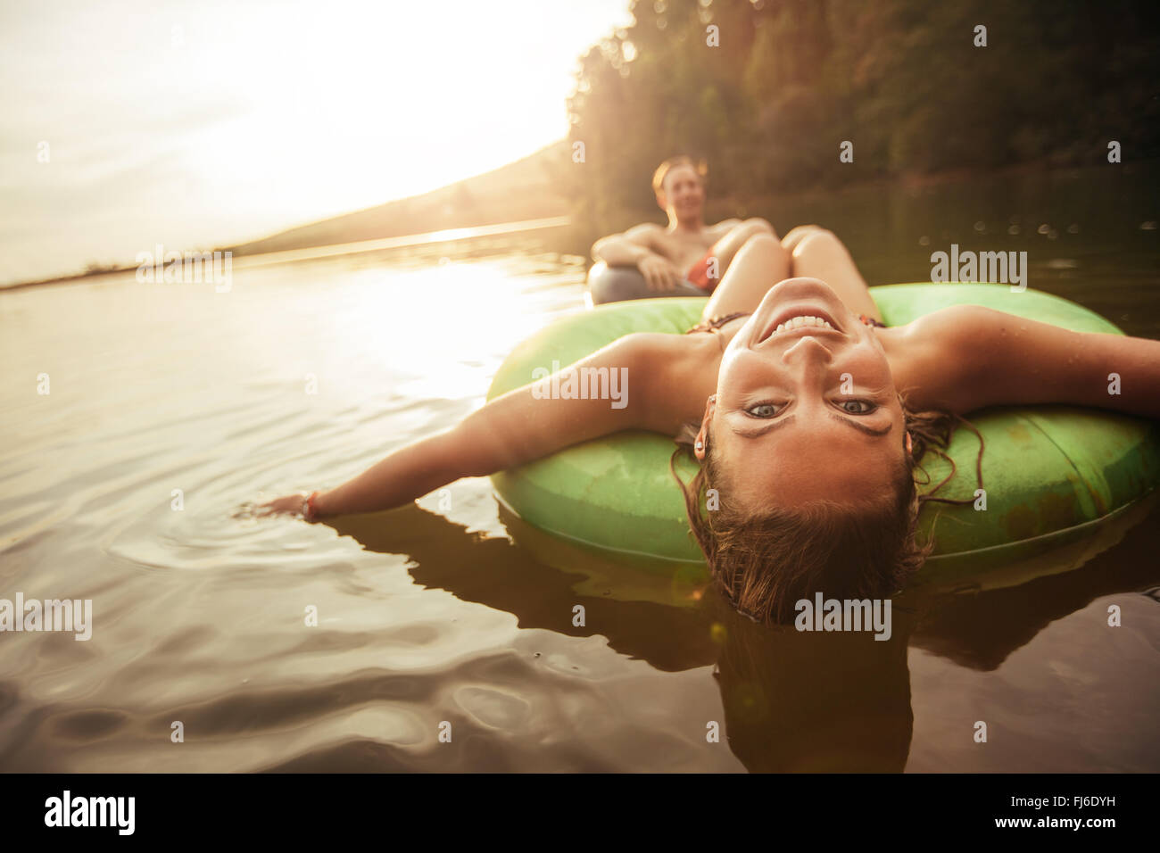 Portrait of happy young woman floating in an innertube with her boyfriend in background at the lake. Young couple - Stock Image
