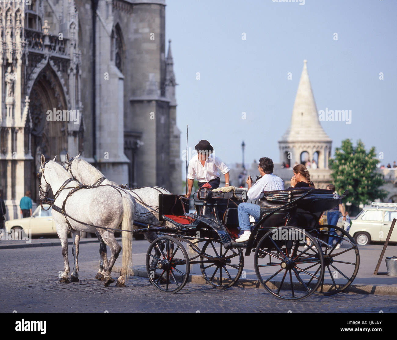 Couple riding on horse carriage outside Matthias Church, The Castle District, Buda District, Budapest, Republic - Stock Image