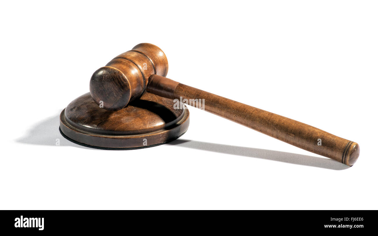 Old wooden judges gavel lying on a plinth over white with a shadow conceptual of law enforcement, justice and sentencing - Stock Image