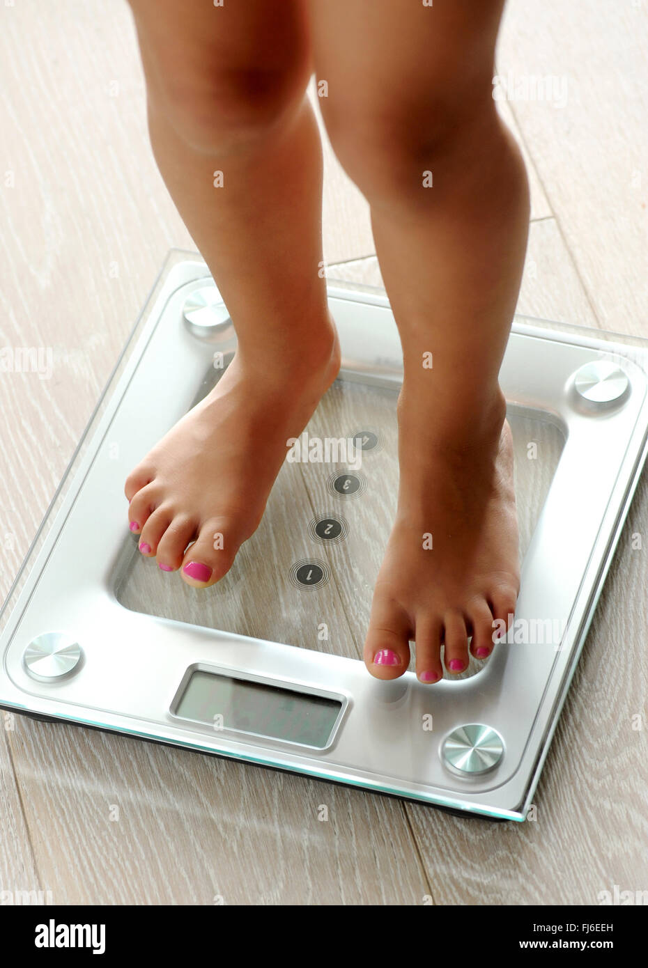 Barefoot woman with manicured toenails standing on a modern glass electronic bathroom scale as she checks her weight - Stock Image