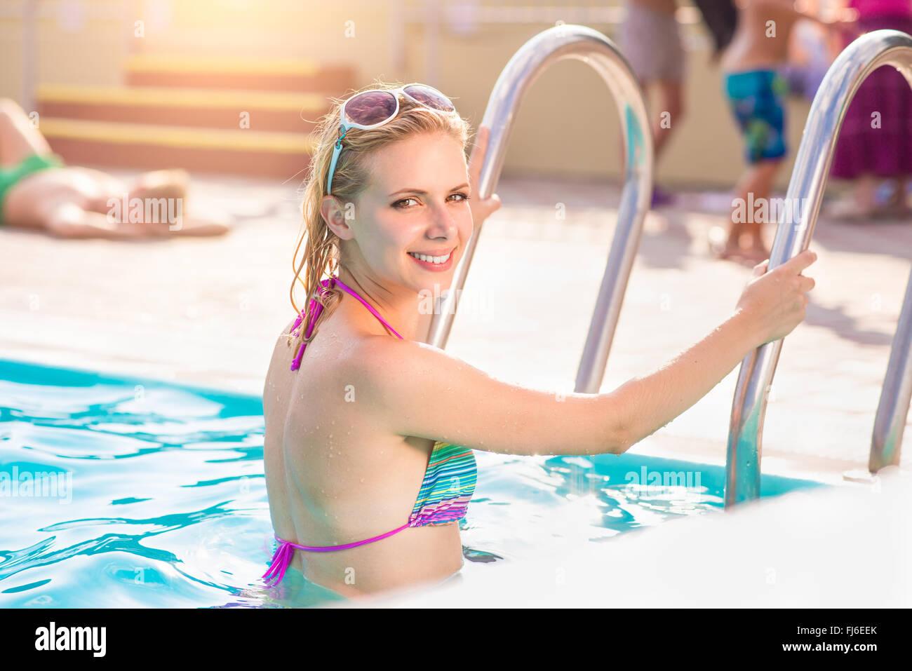 Woman in bikini standing on the pool stairs - Stock Image