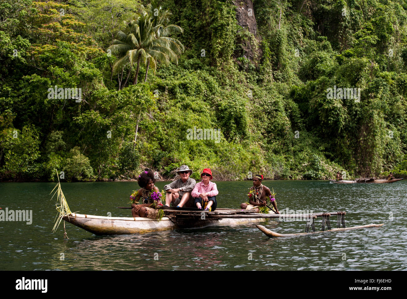 Tourists on traditional canoe Maclaren Harbour, Papua New Guinea - Stock Image