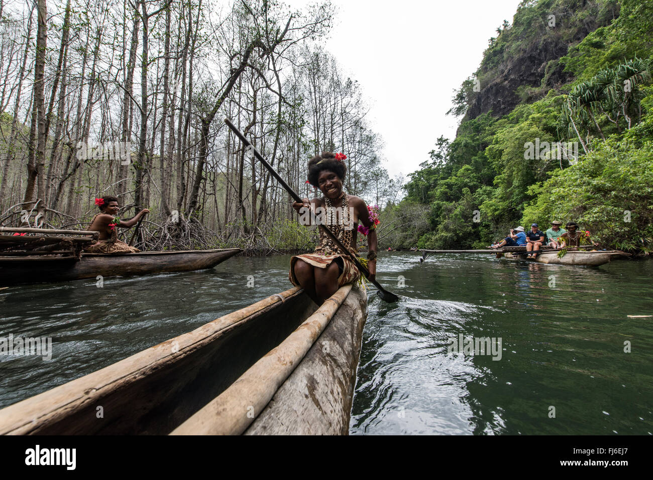 Young Girl paddling traditional canoe Maclaren Harbour, Papua New Guinea - Stock Image