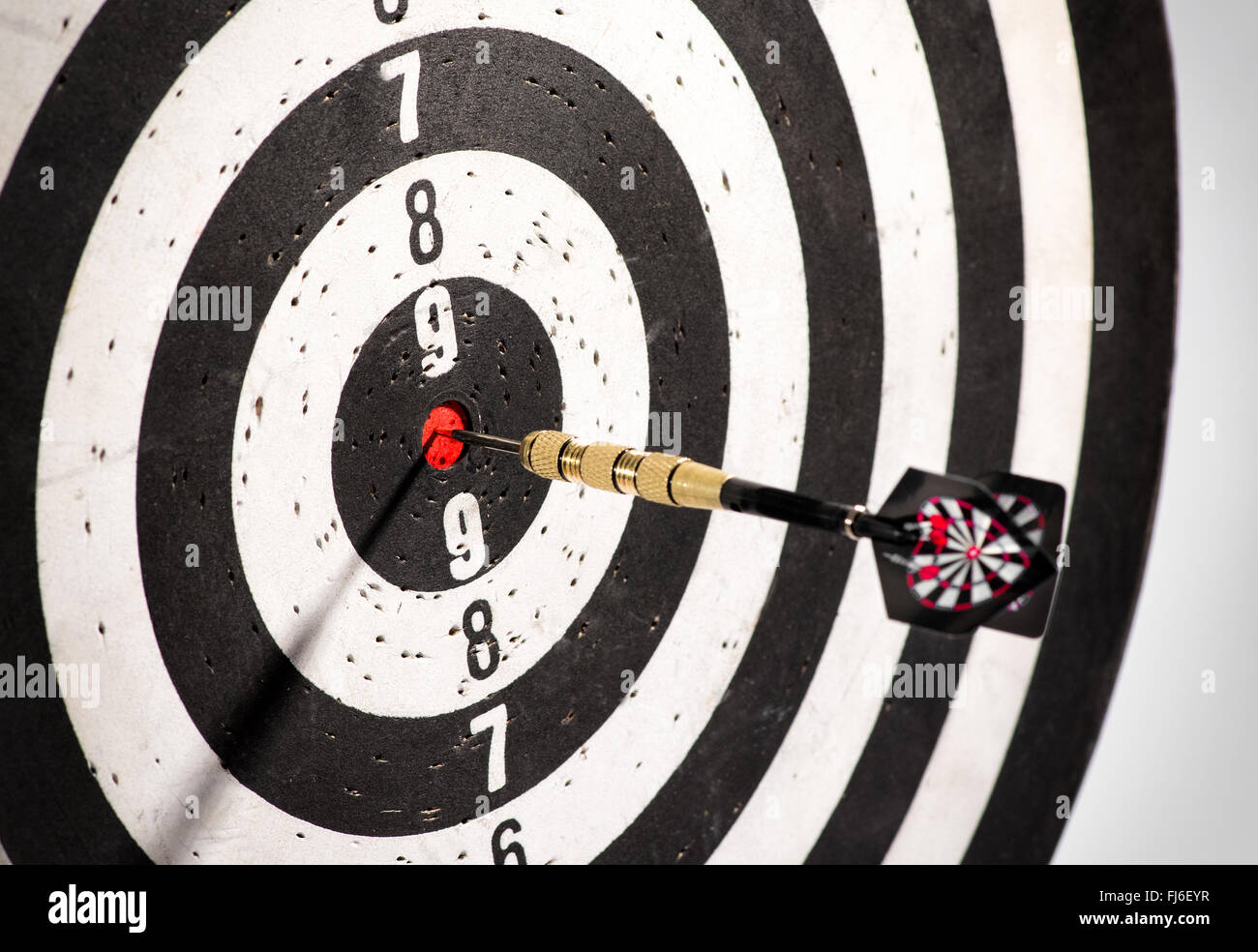 Dart in the bulls eye center of a dart board or black and white target - Stock Image
