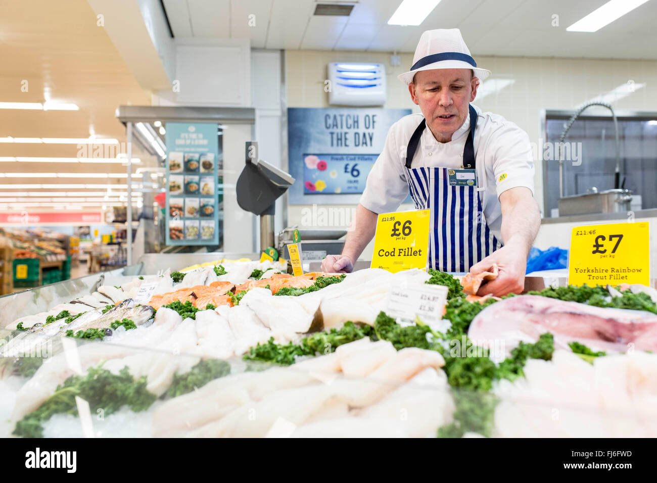 A fishmonger at a Morrisons fresh look store - Stock Image