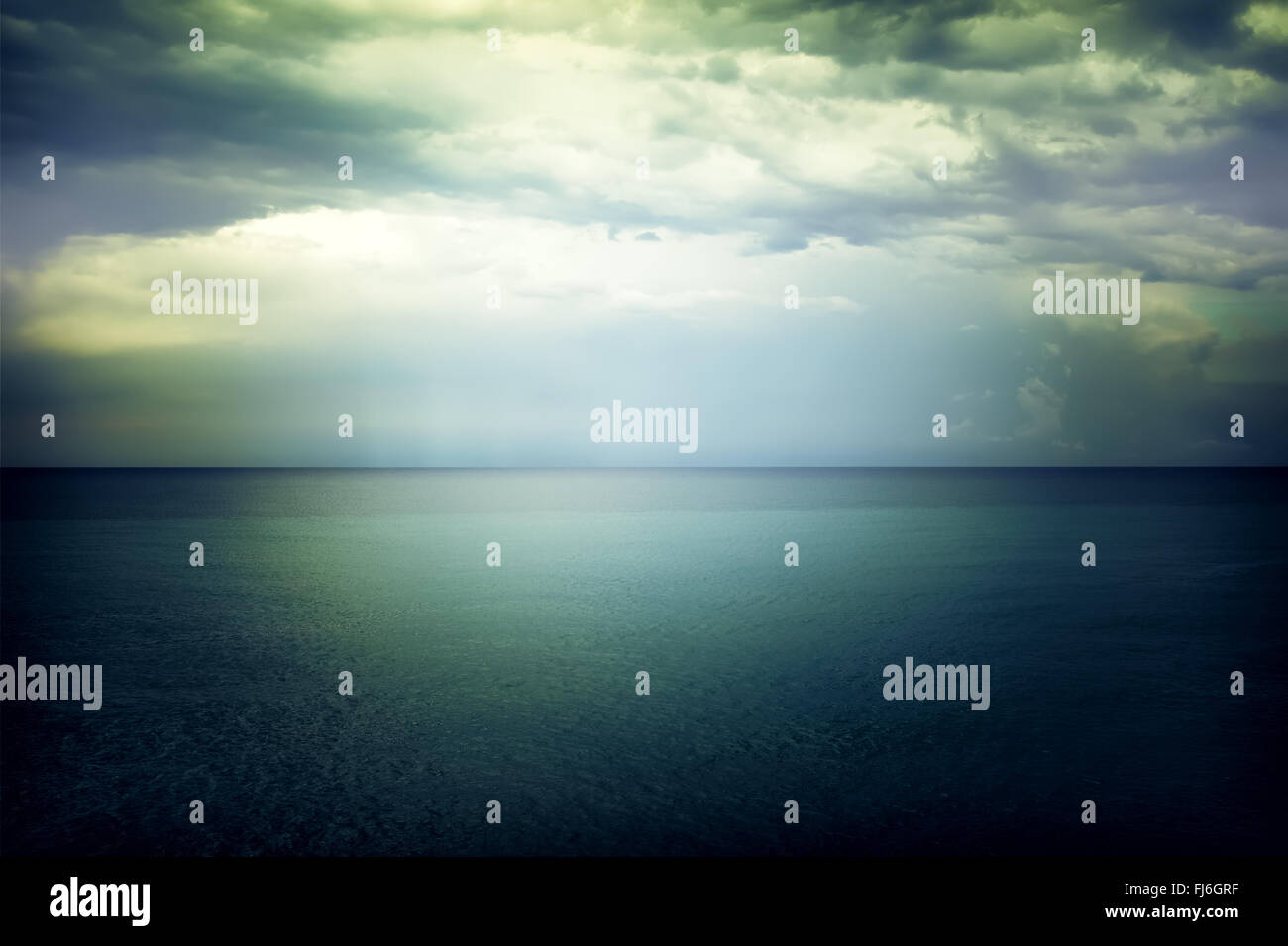 Light in the sky above the gloomy dark blue sea. Mediterranean nature. - Stock Image
