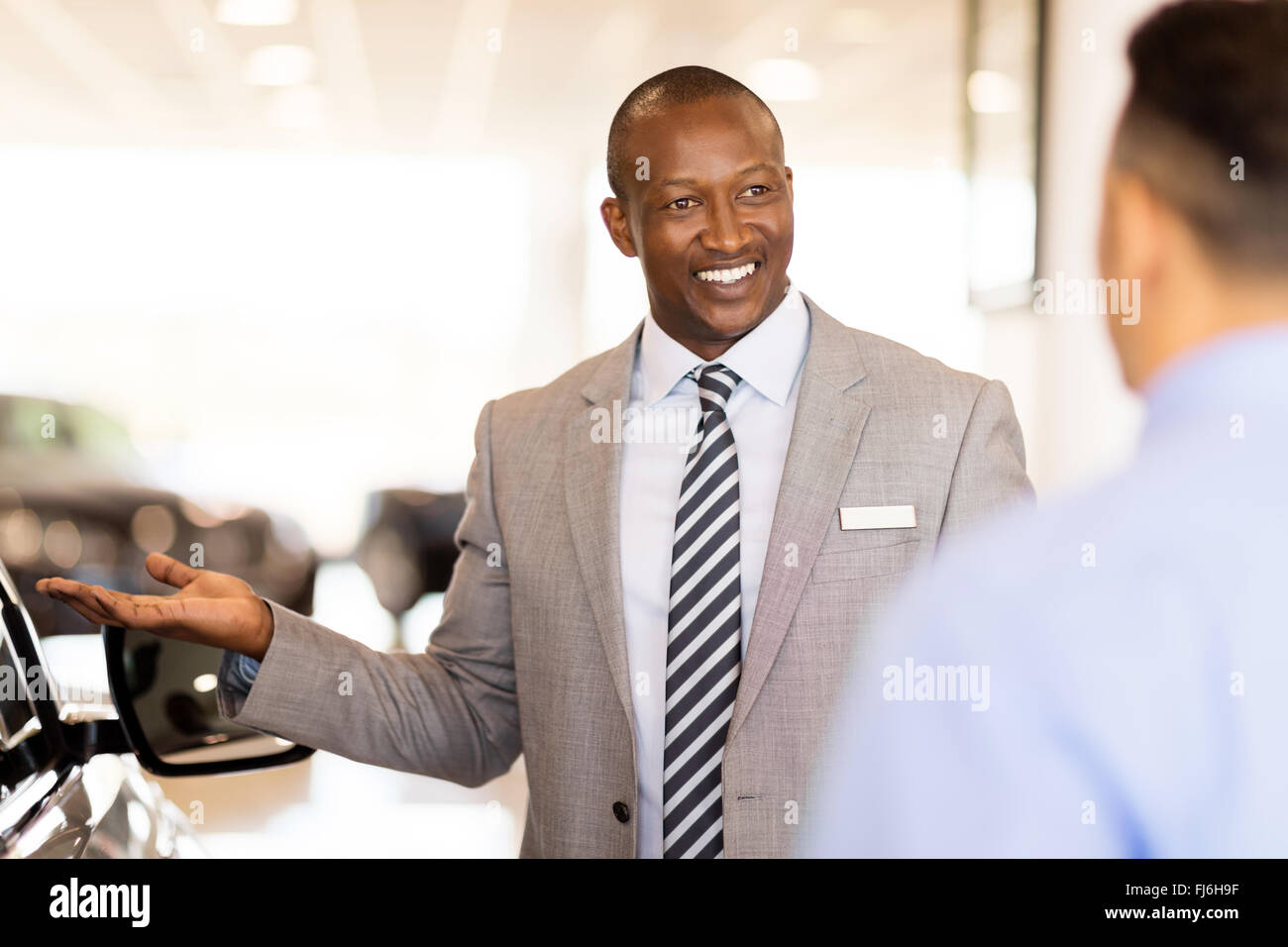 handsome African salesman presenting new car to clients - Stock Image
