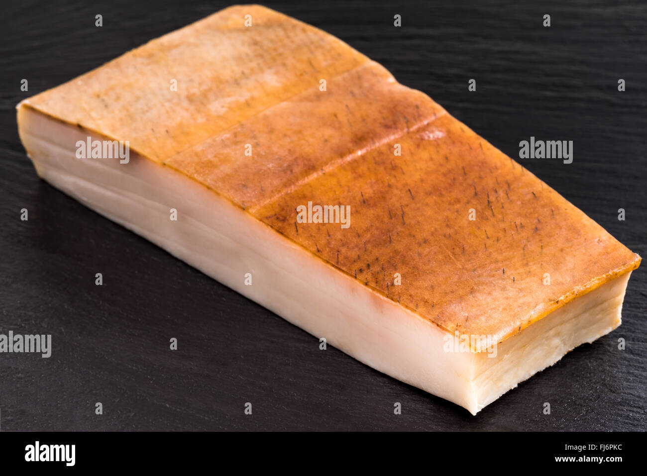 Fat bacon on a black background, bill, pork belly, rind, smoked, skin, calories, diet, flavor, plate, postion, white, - Stock Image