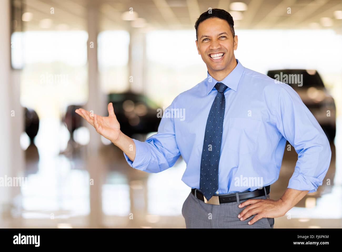 friendly vehicle salesman presenting new cars at showroom - Stock Image