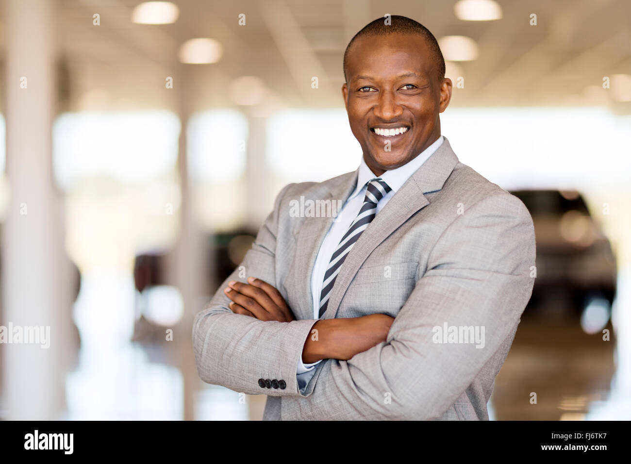 African car sales consultant with arms folded in showroom - Stock Image
