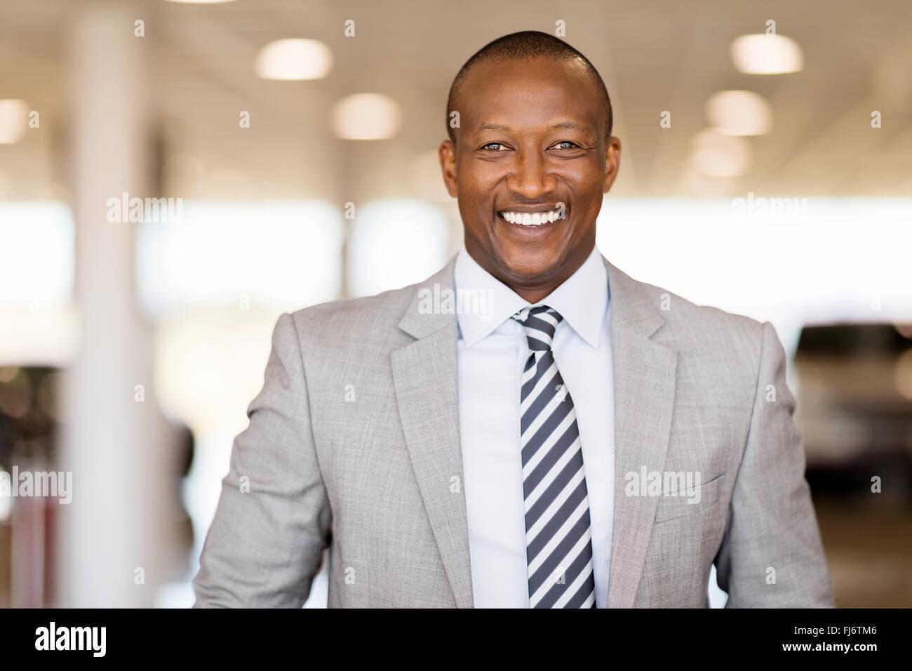 happy African car salesman in showroom - Stock Image