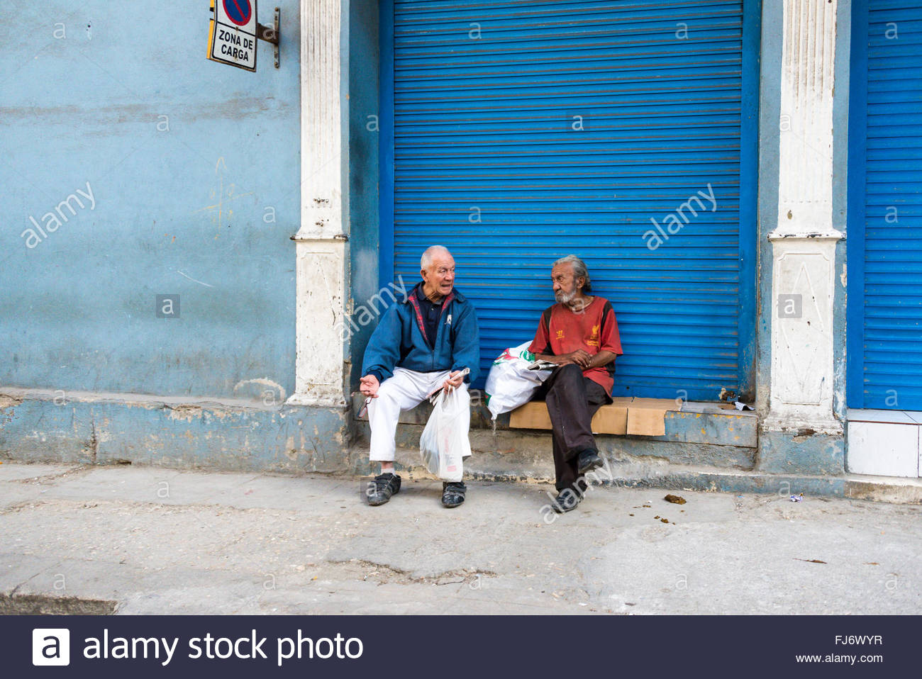 Cuban seniors lifestyle: Two senior men sitting out on the street. With usually good weather, retired people  usually - Stock Image