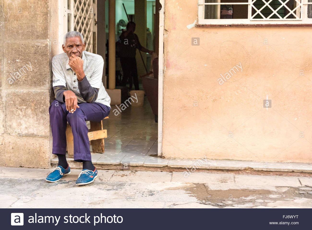 Cuban senior sitting at his door watching the everyday life. Good weather temperatures allows an easy outdoor lifestyle - Stock Image