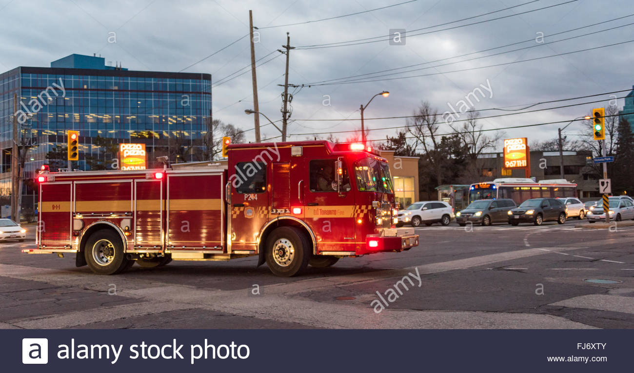 Firetruck from fire department swiftly going to an emergency call, late in the afternoon. - Stock Image