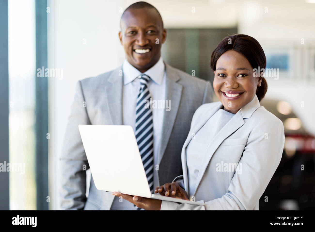 portrait of two workers with laptop inside car showroom - Stock Image