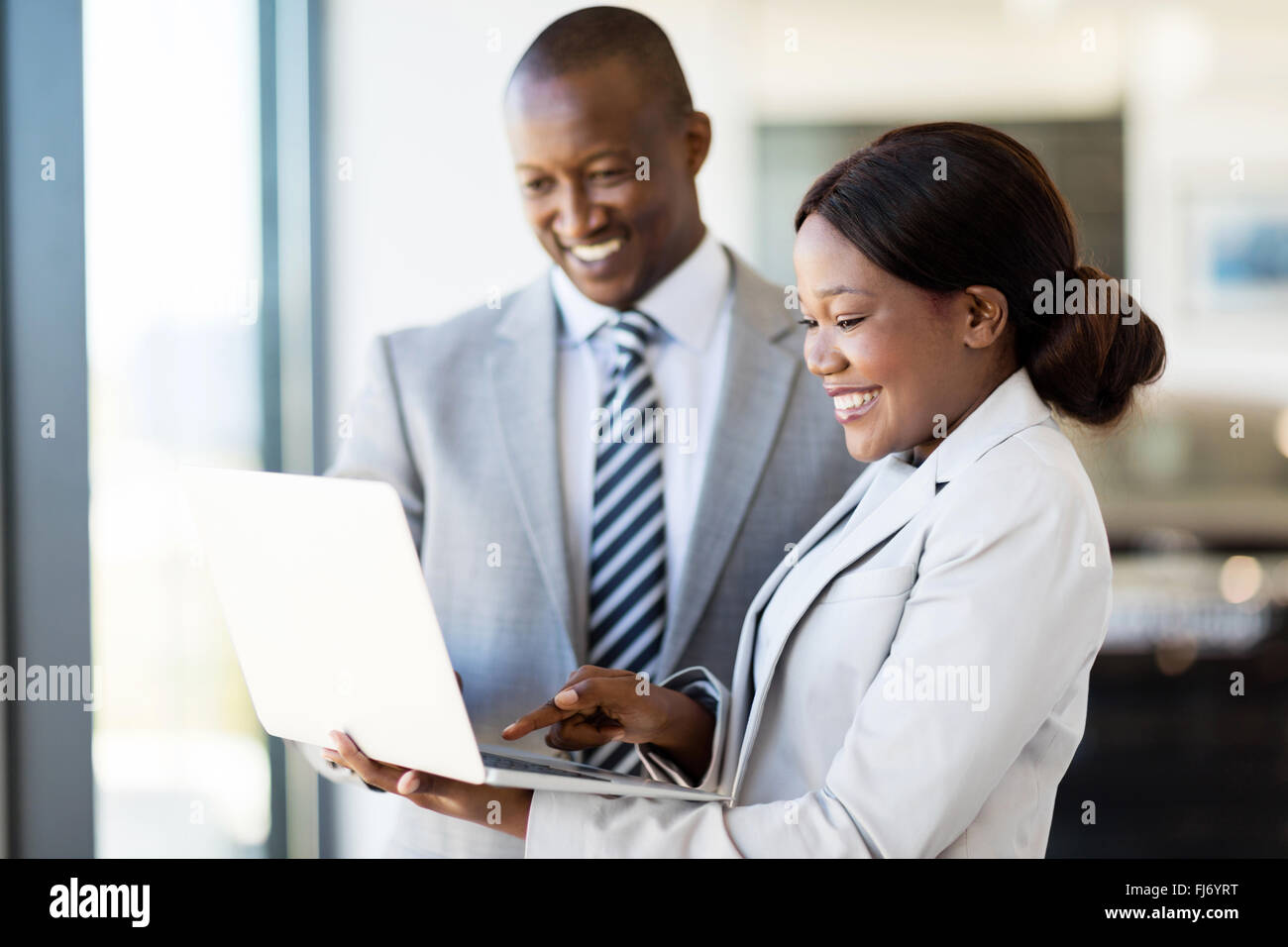 professional car sales consultants working on laptop computer inside vehicle showroom - Stock Image