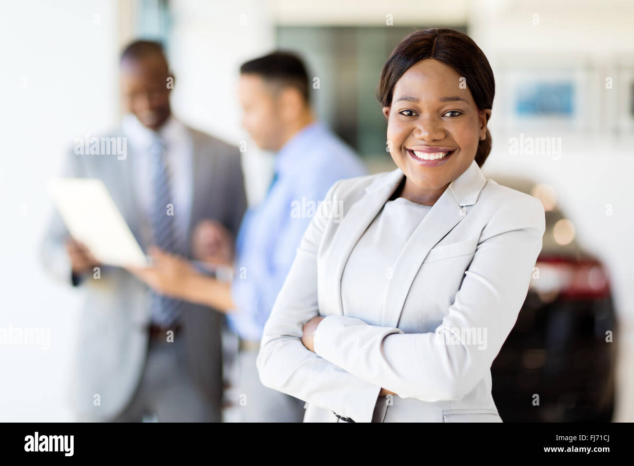 beautiful young African saleswoman standing inside vehicle showroom - Stock Image