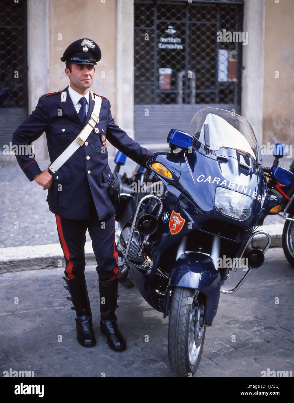 Italian policeman (Carabinieri) standing by motorbike, Rome, Rome Province, Lazio Region, Italy - Stock Image