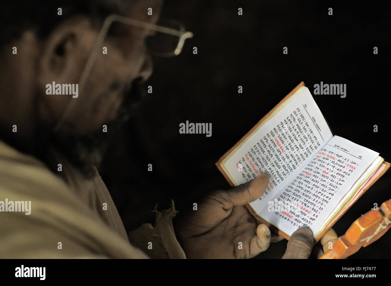 Orthodox priest reads Holy Scriptures inside Mikael Milhaizengi rock-hewn church in the Tigray Region, Ethiopia - Stock Image