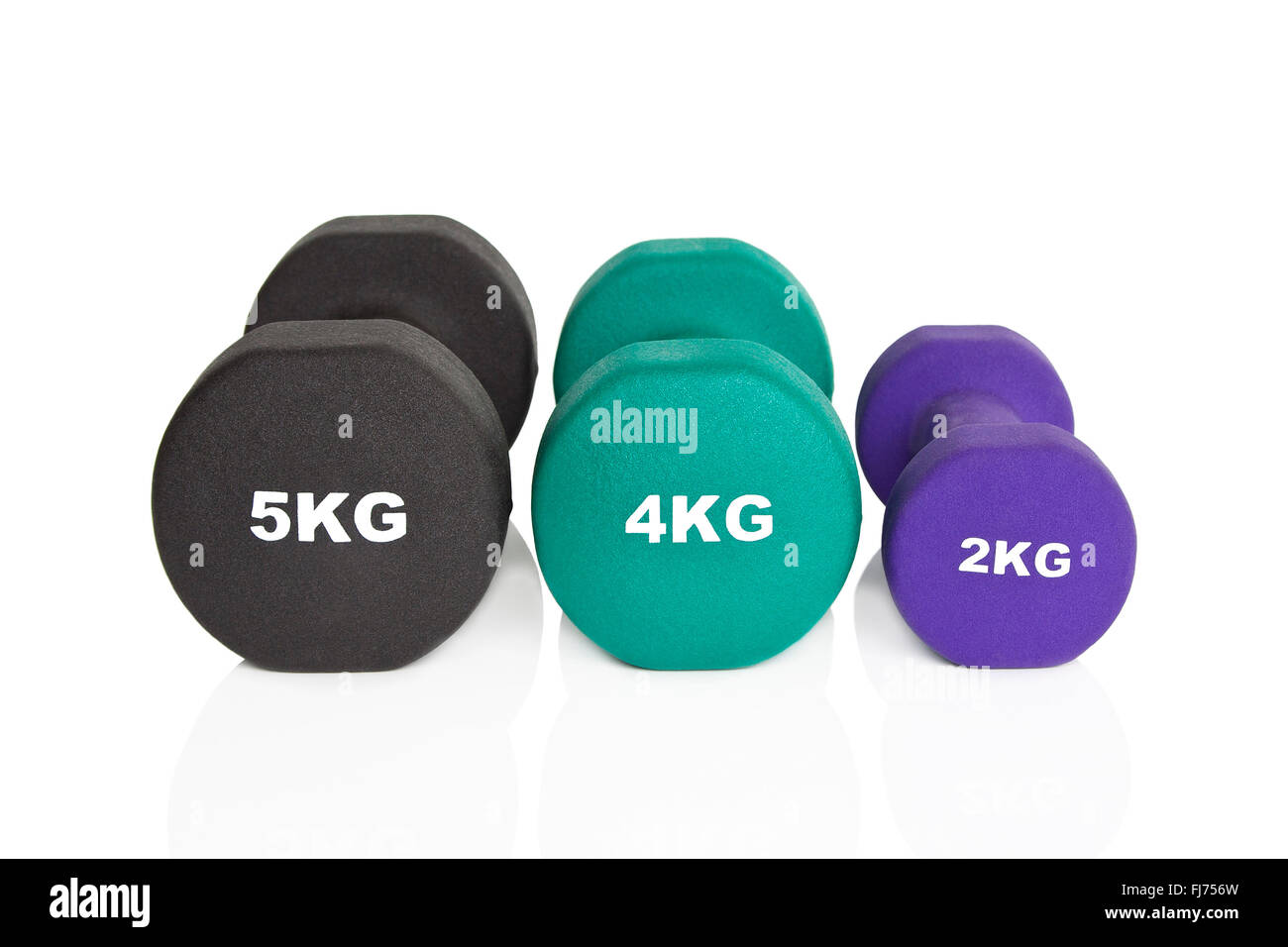 Black, green and purple dumbbells isolated on white background. Weights for a fitness training. - Stock Image