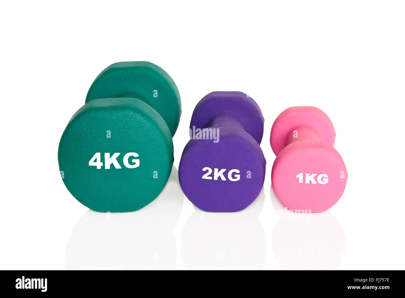 Pink, green and purple dumbbells isolated on white background. Weights for a fitness training. - Stock Image