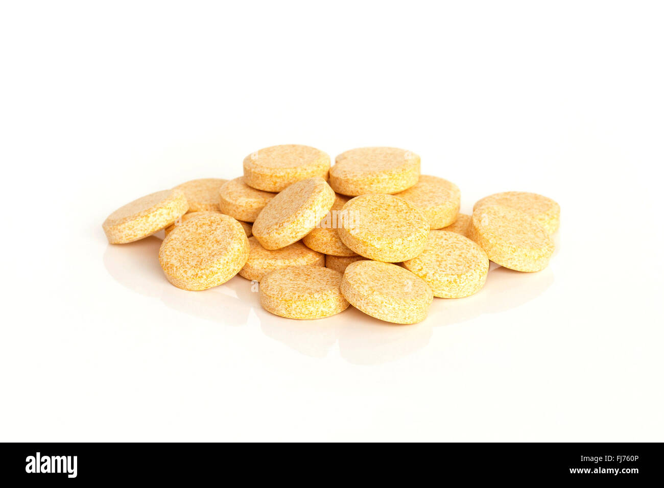 A pile of vitamin C supplement tablets isolated on a white background. - Stock Image