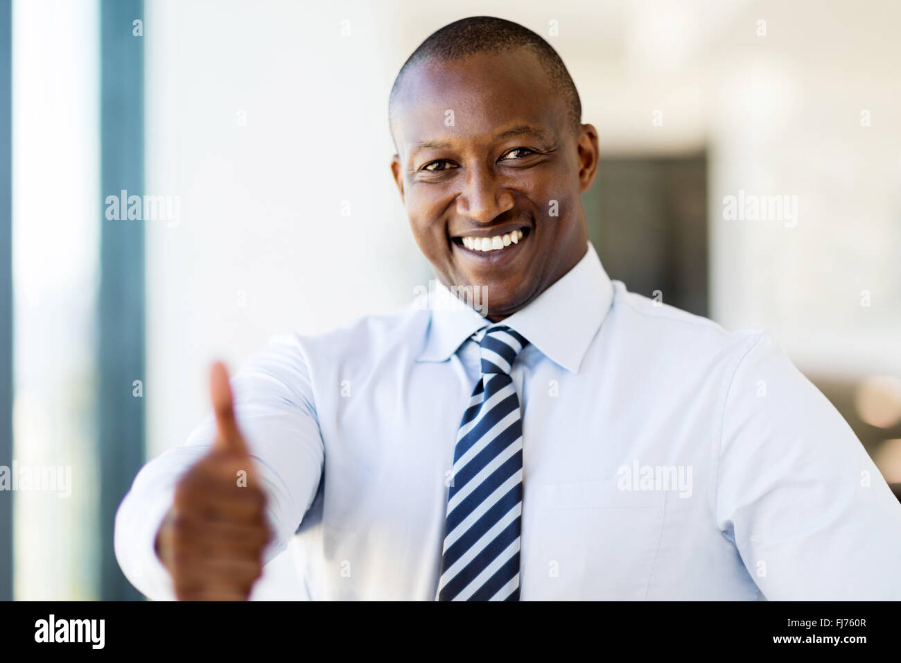 happy black business man giving thumb up in modern office - Stock Image