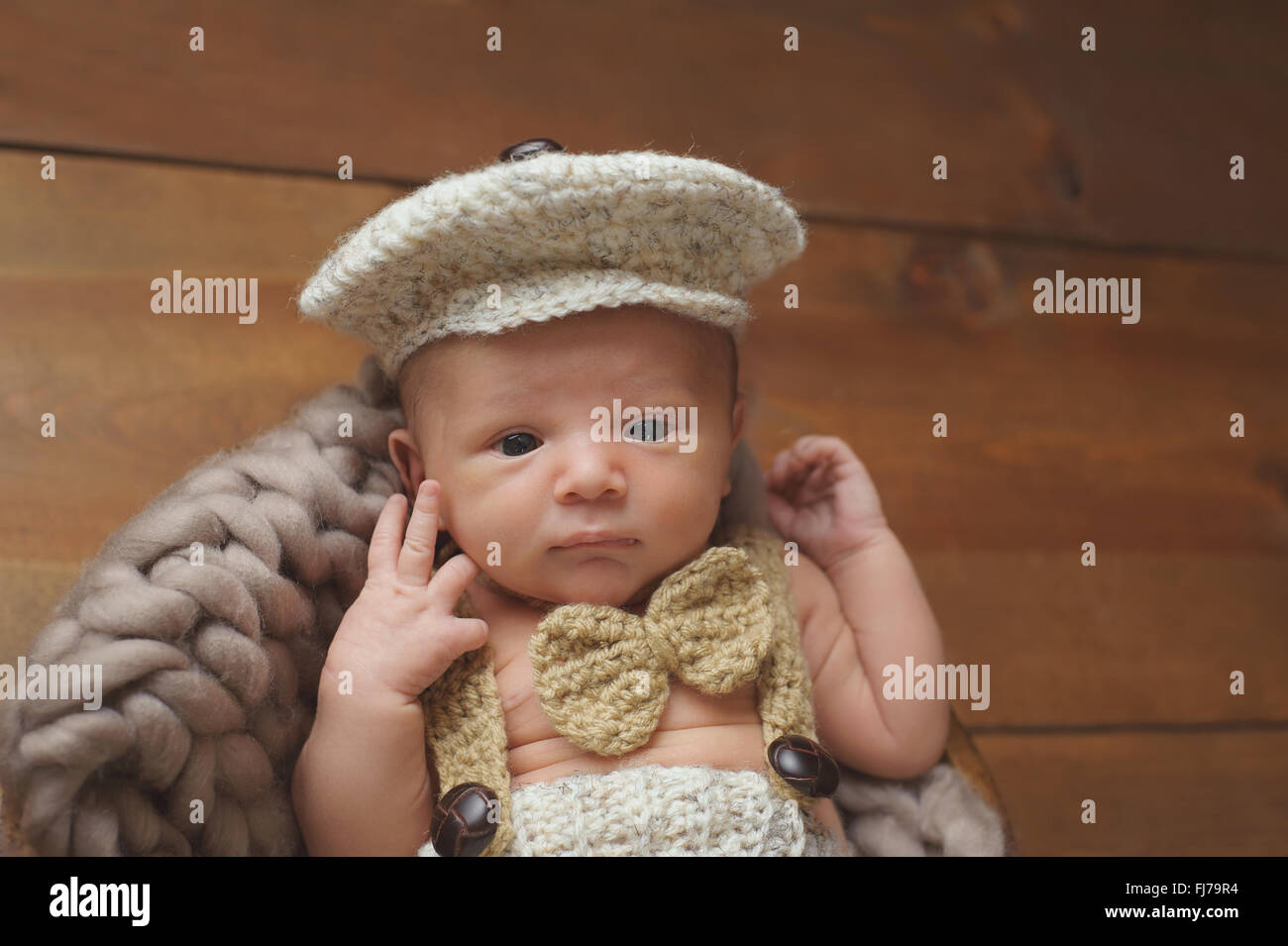 Newborn Baby Boy Wearing a Newsboy Cap and Bowtie - Stock Image