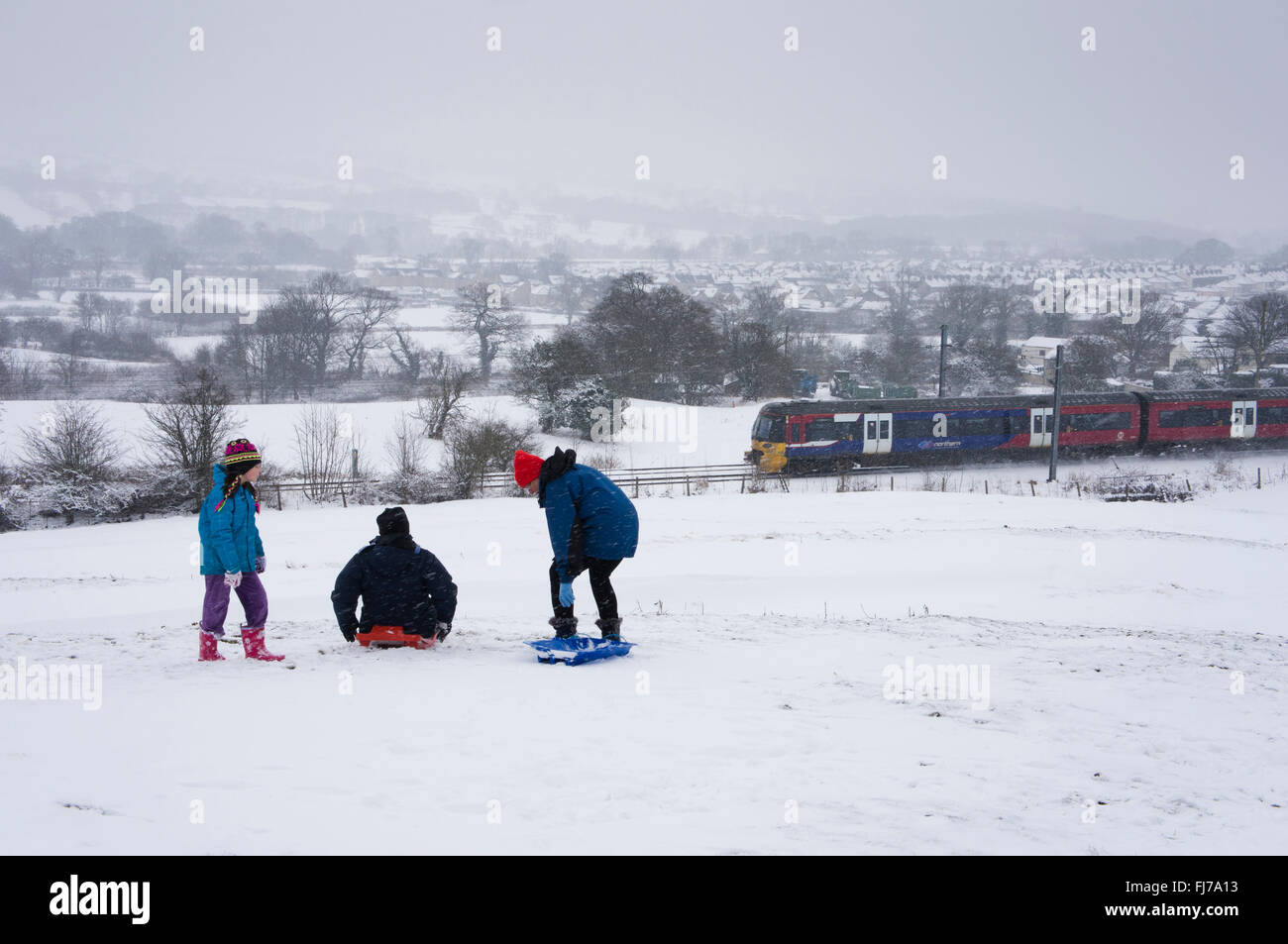 Winter countryside scene - in the snow, a family of 3 with sledges, whilst a train travels past beyond - Burley Stock Photo