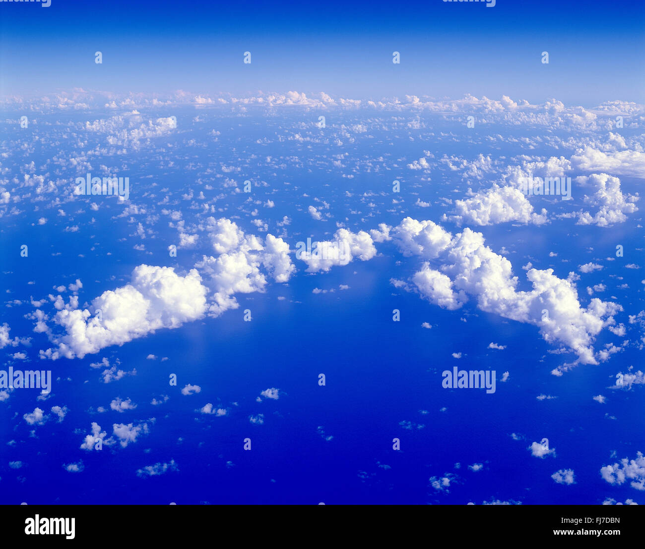 Aerial view of clouds from aircraft over sea - Stock Image
