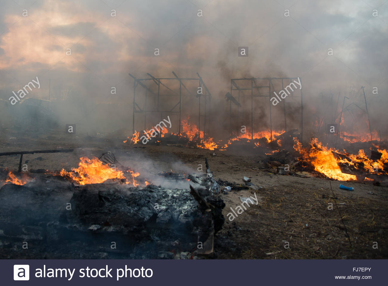 Calais, France. February 29th, 2016. Fires set by just-evicted refugees ravage the 'Jungle' migrant camp - Stock Image