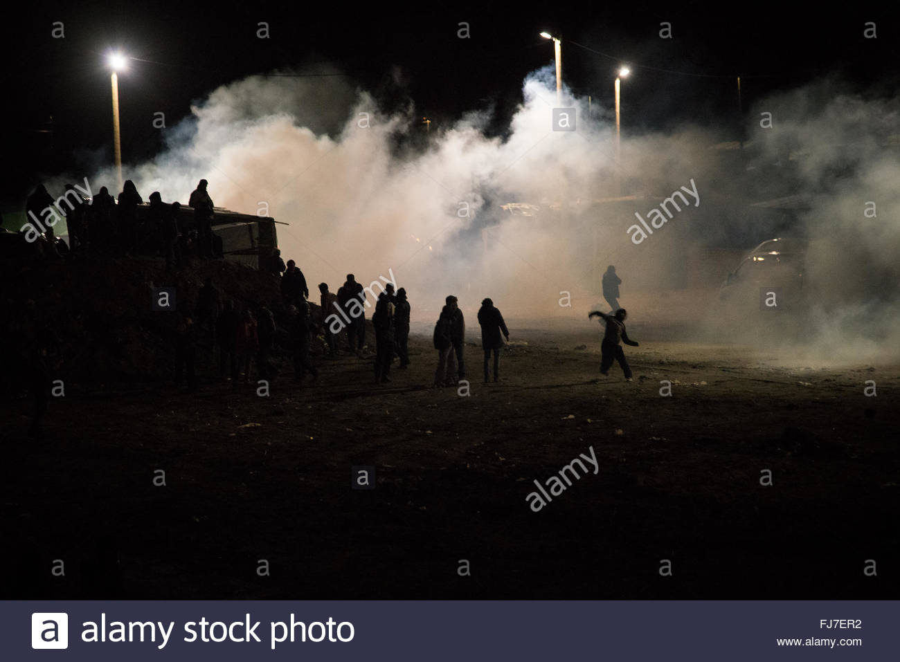 Calais, France. February 29th, 2016. Just-evicted refugees run through tear gas as authorities dismantle the 'Jungle' - Stock Image