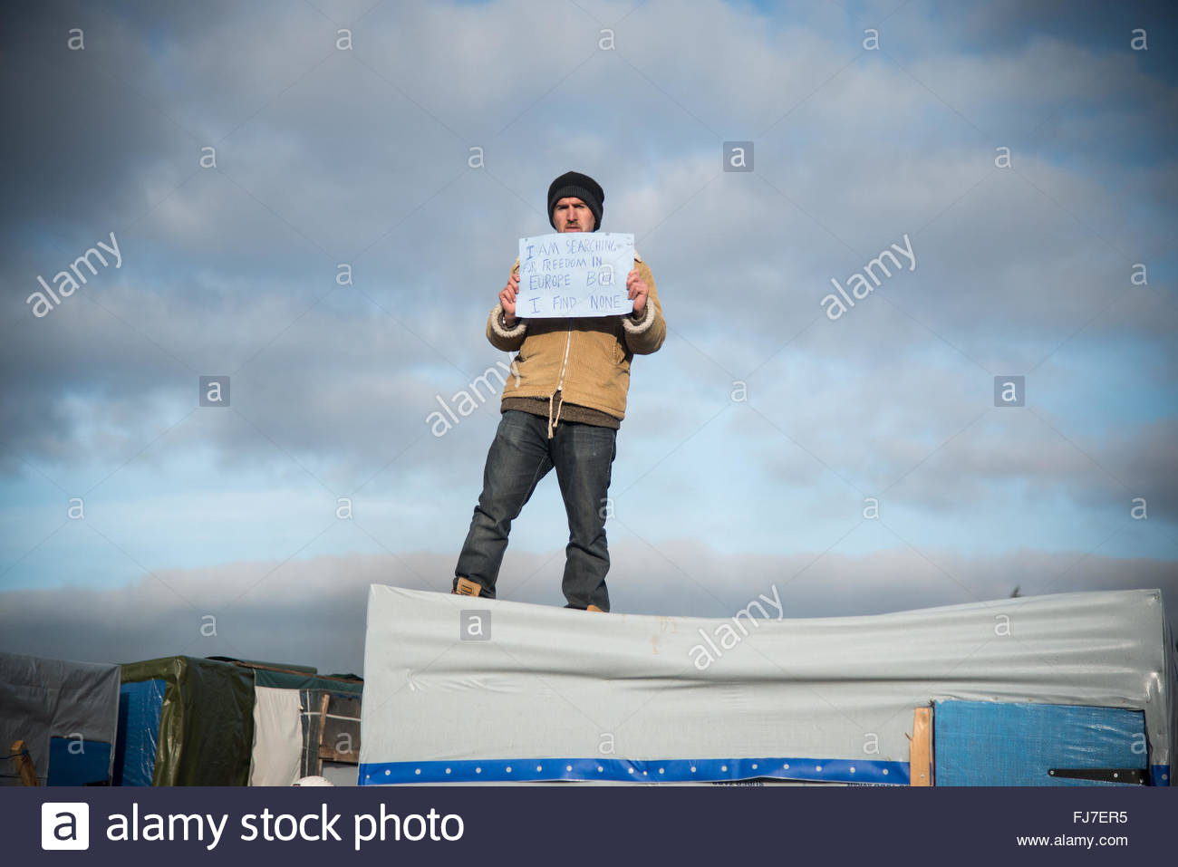 Calais, France. February 29th, 2016. A just-evicted refugee stands atop a makeshift campsite as authorities dismantle - Stock Image