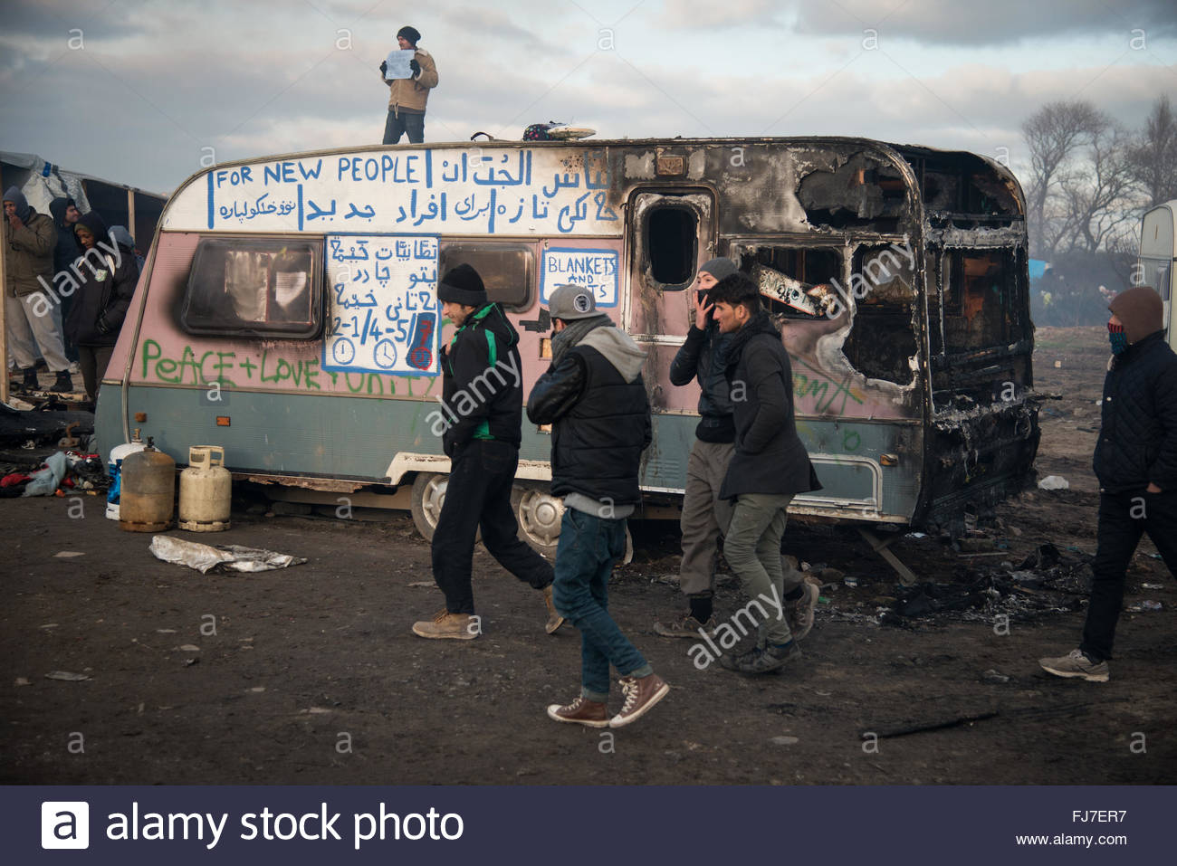 Calais, France. February 29th, 2016. Just-evicted refugees walk past a burned-out home as authorities dismantle - Stock Image