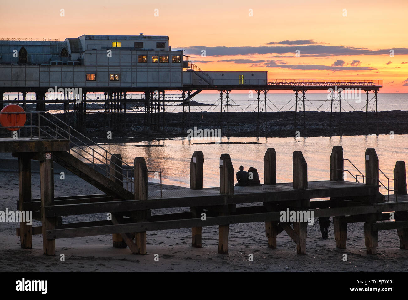 Couple watching setting sun,sunset after watching starlings at Aberystwyth Pier,Aberystwyth,at sunset.Ceredigion,Wales,U.K. Stock Photo