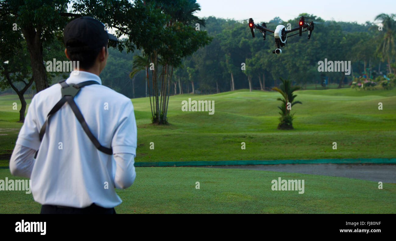 Asian men flying a drone in a park - Stock Image