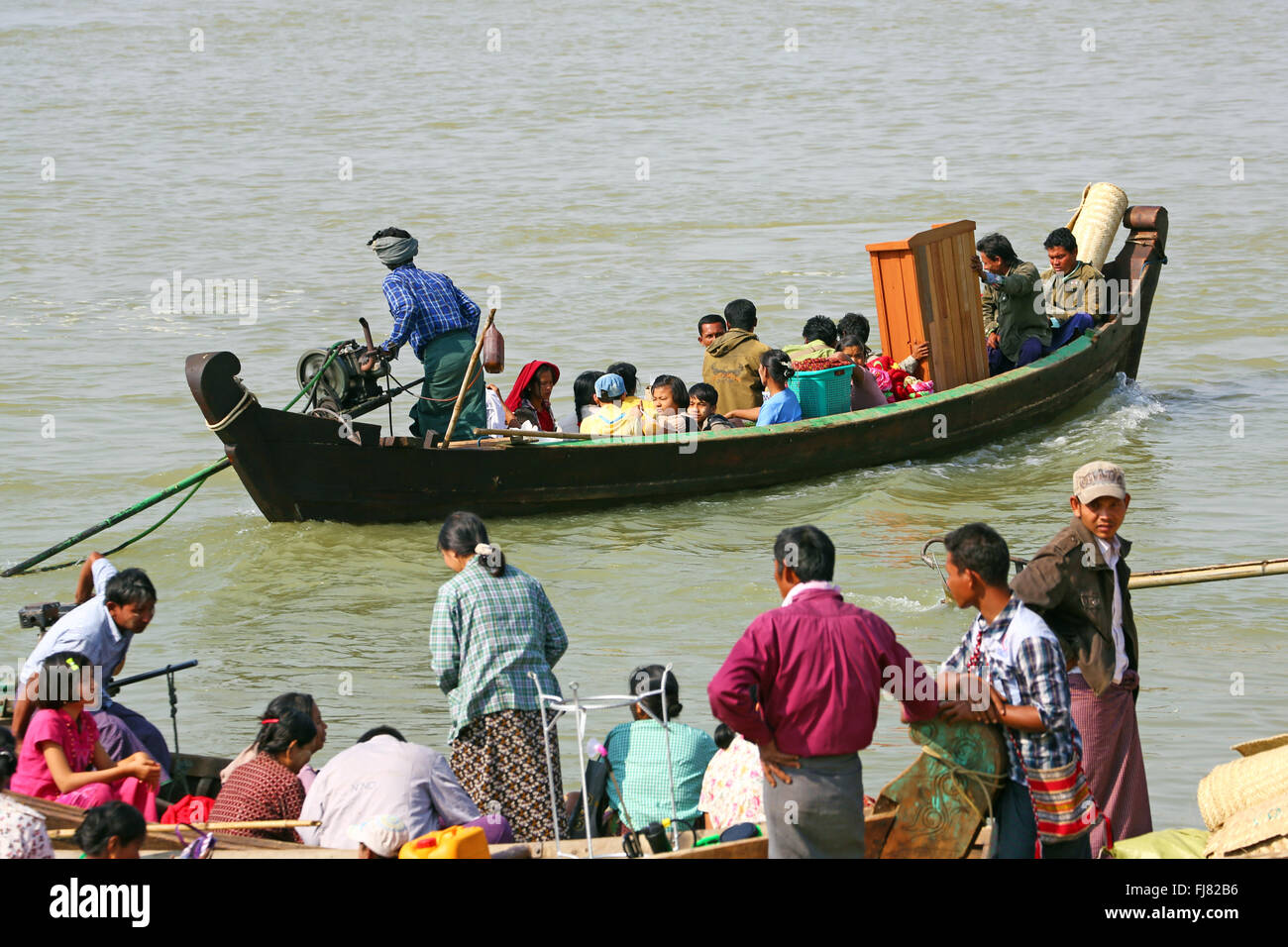 People loading and unloading ferry boats on the Ayeryarwaddy River in Old Bagan, Bagan, Myanmar (Burma) - Stock Image