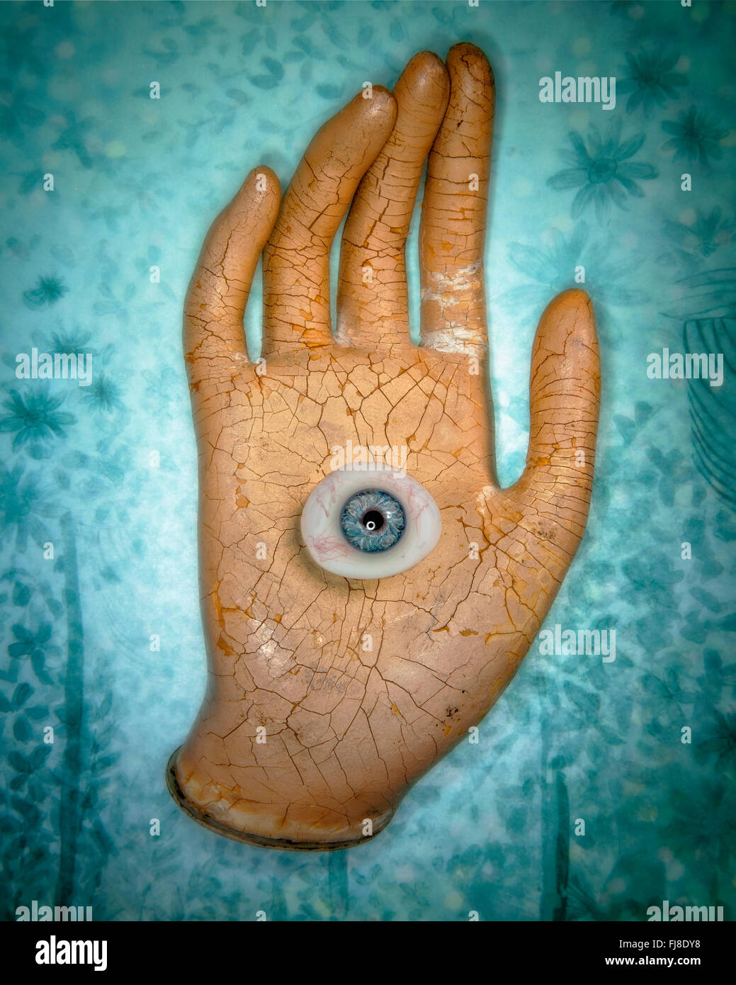 A glass eyeball in the palm of a mannequin hand on blue background. - Stock Image
