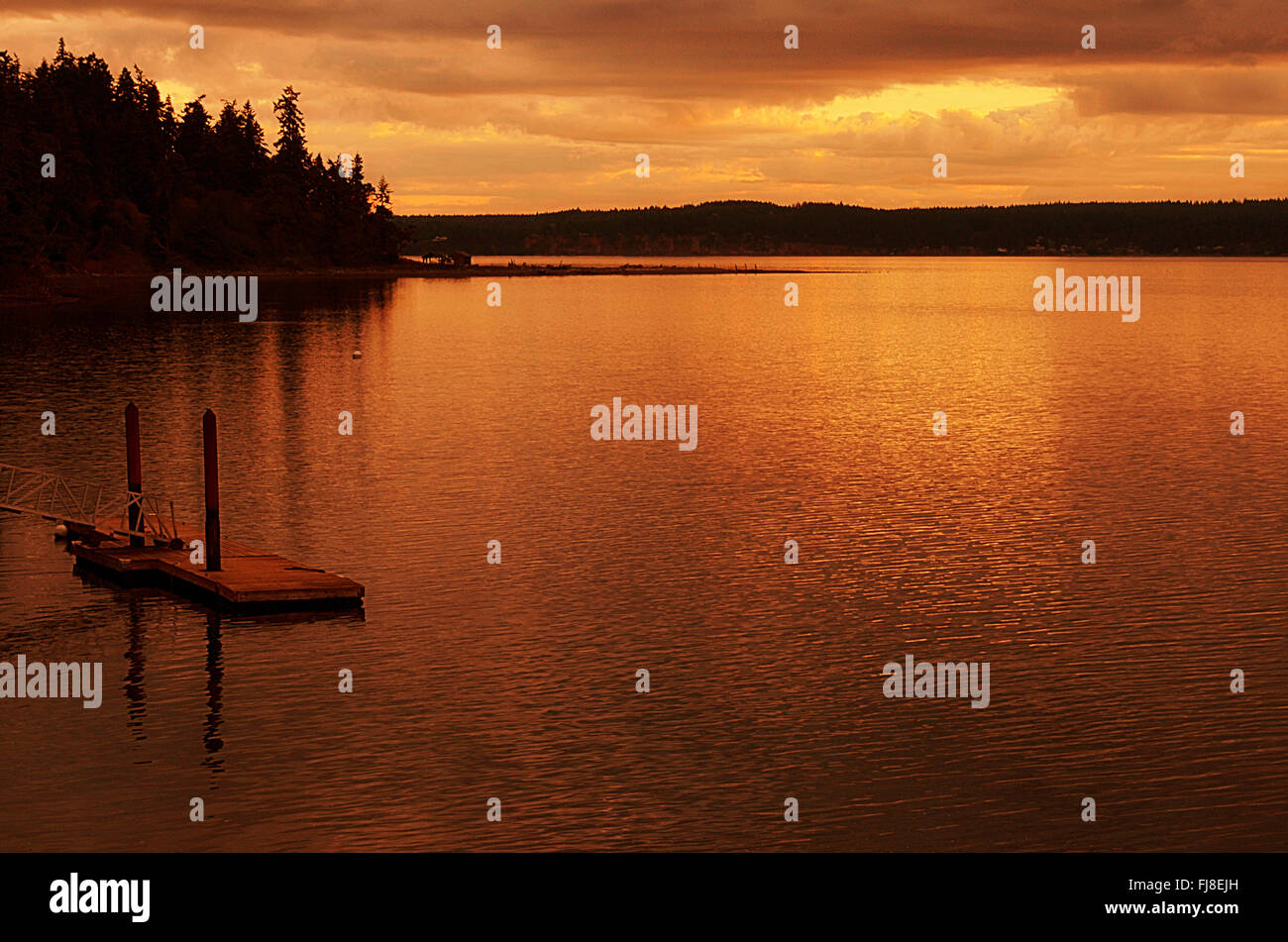 Sunrise over Discovery Bay, WA. Boat dock, no boat, deep orange brown sky reflecting off water. - Stock Image