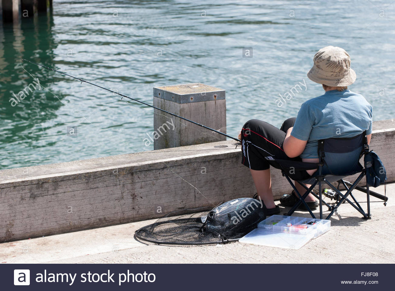 Young boy sitting fishing from the harbourside at West Bay, Dorset Stock Photo