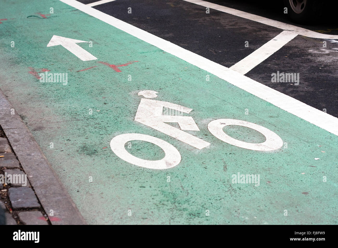 Green paint on road designating a dedicated bike lane with a bike rider symbol and arrow painted in white on ground - Stock Image