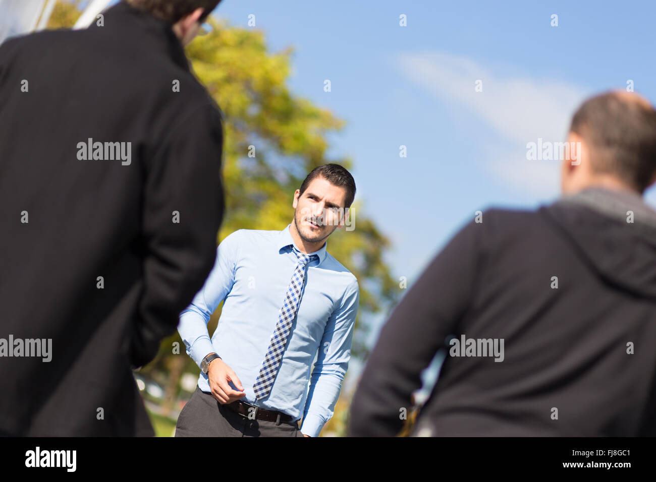 Businessman being approached and blackmailed by two racketeers. Stock Photo